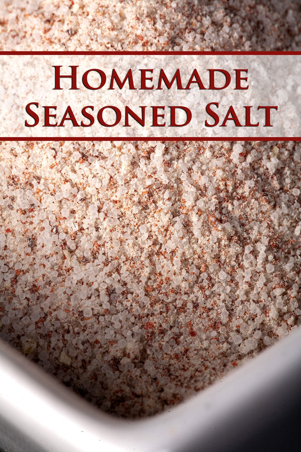 A small, square shaped white bowl with a pinkish homemade seasoned salt mixture in it.
