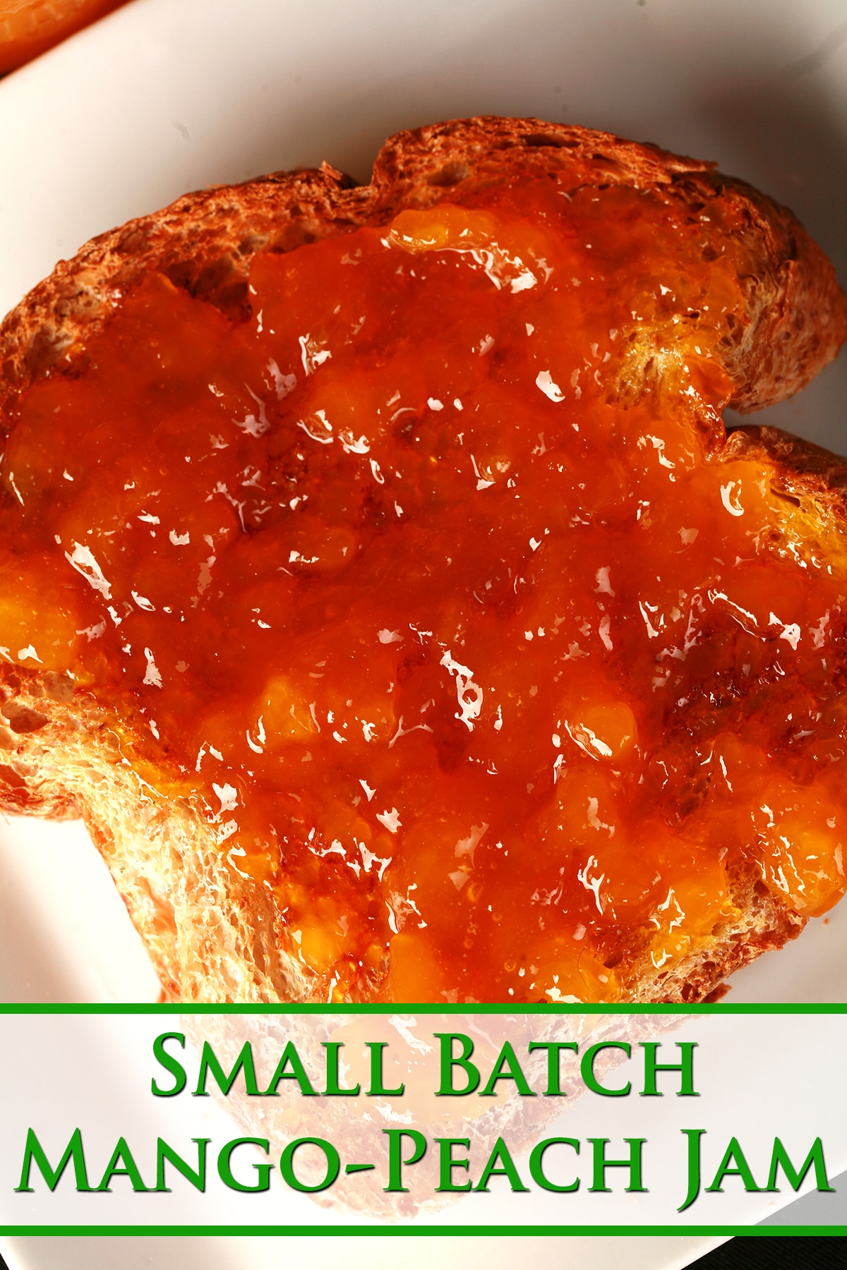 A close up view of a slice of toast that is generously spread with mango peach jam.