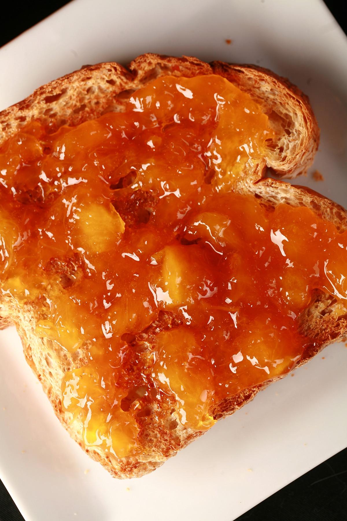 A slice of toast spread with chunky peach jam.