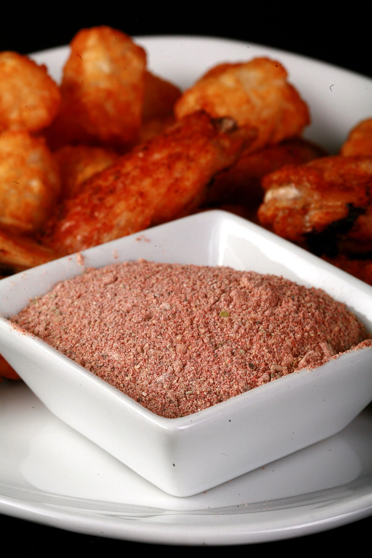 A small, square white bowl of a deep orange-red dry rub, on a larger plate of wings and tater tots. The wings are coated in the same red dry rub.