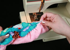 Hands feeding a piece of terrycloth through a sewing machine