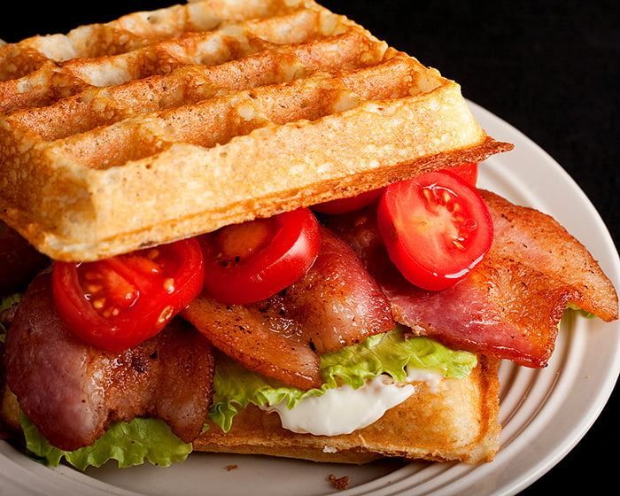 A waffle sandwich on a white plate.  The sandwich is willed with bacon, lettuce, tomatoes, and mayo.