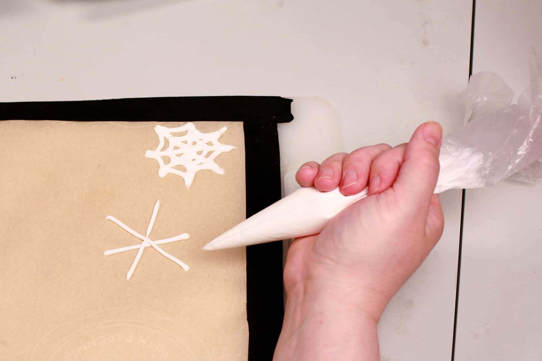 A hand uses a pastry bag full of white royal icing to pipe spider webs on a parchment lined baking sheet.