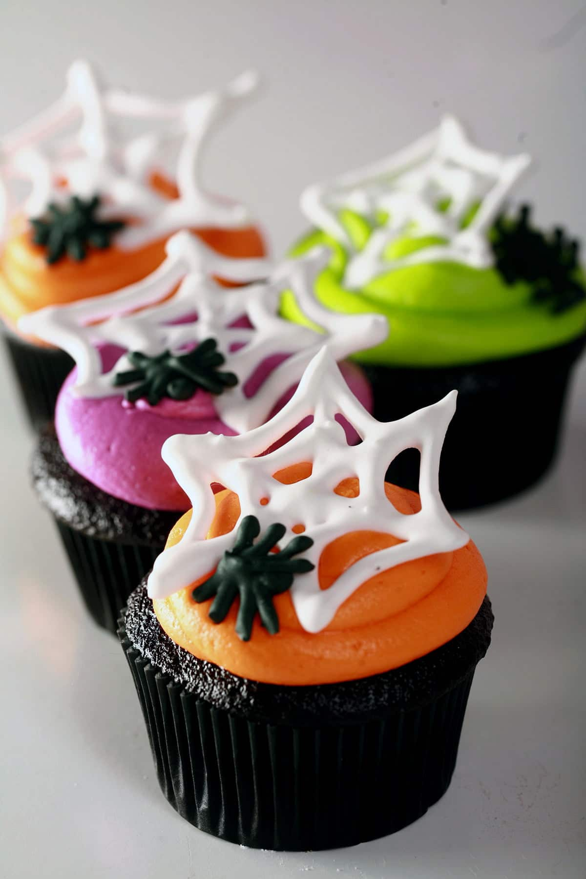 4 black velvet cupcakes frosted with brightly coloured icing - lime green, electric purple, and orange - are shown topped with royal icing spider webs and spiders.