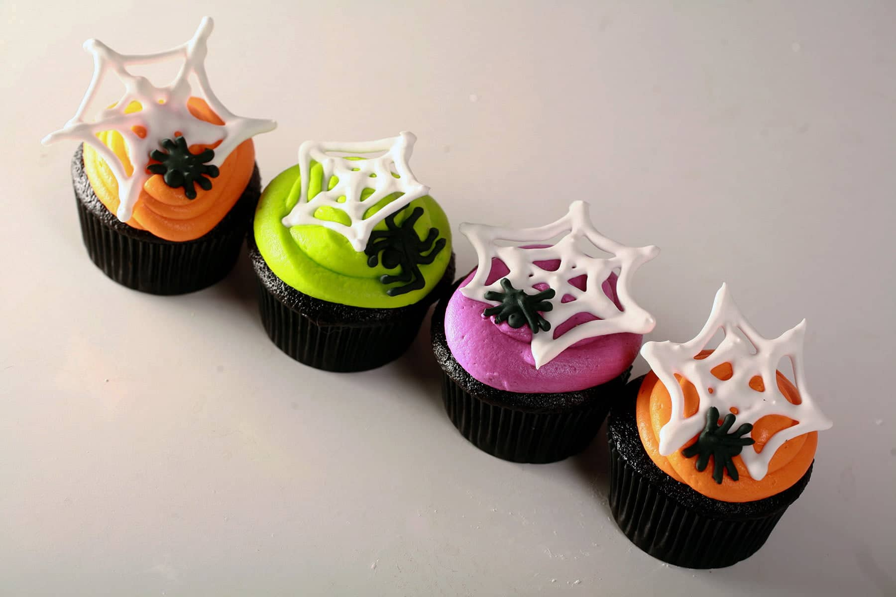 4 black velvet Halloween cupcakes frosted with brightly coloured icing - lime green, electric purple, and orange - are shown topped with royal icing spider webs and spiders.