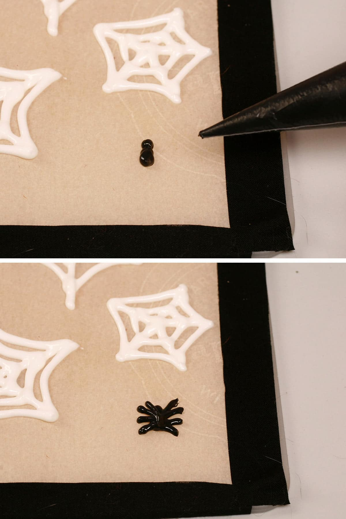 A hand uses a pastry bag full of black royal icing to pipe spiders on a parchment lined baking sheet.
