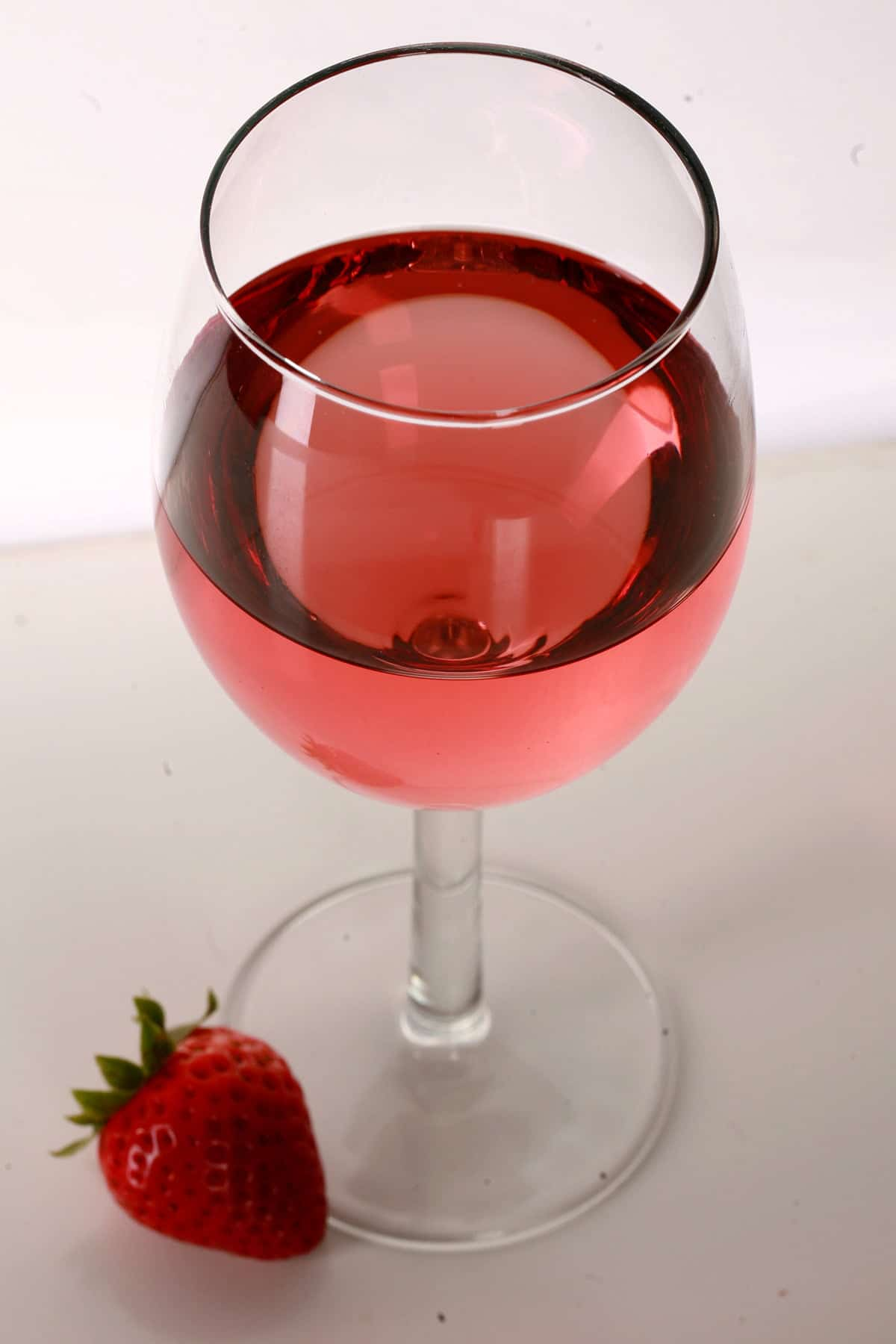 A glass of pale red strawberry wine is pictured, with a single strawberry at the base of the glass.