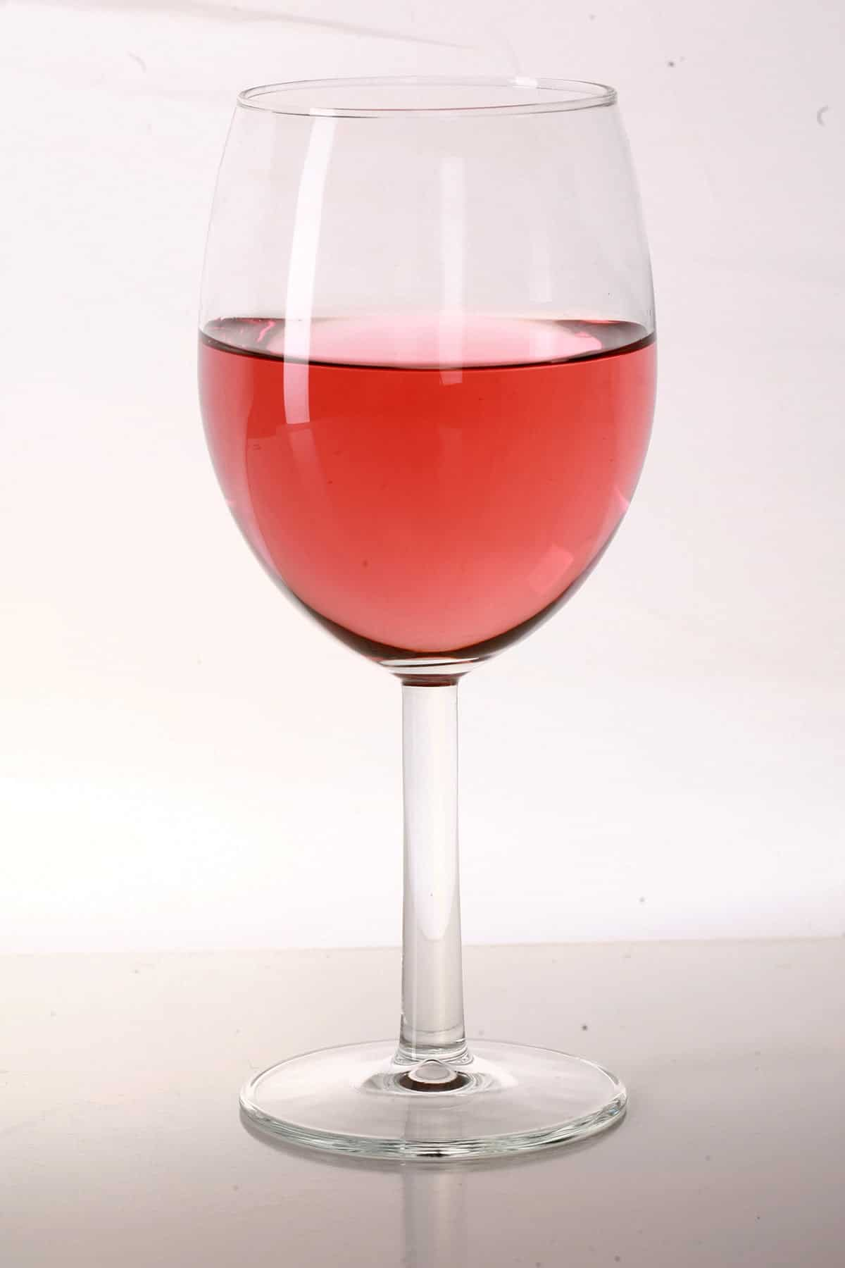 A glass of pale red strawberry wine, made with this strawberry wine recipe.