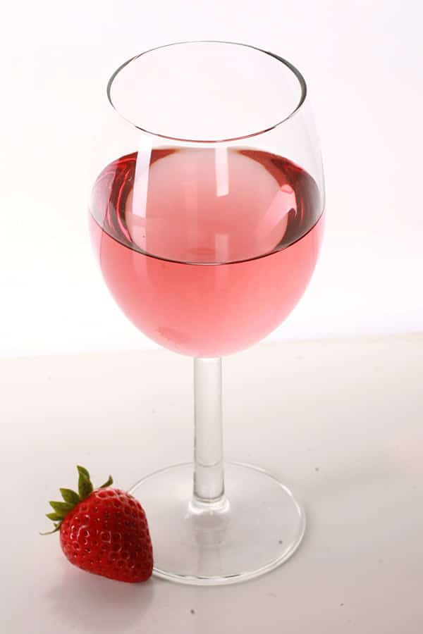 A stem glass of a deep pink wine, with a strawberry at the base