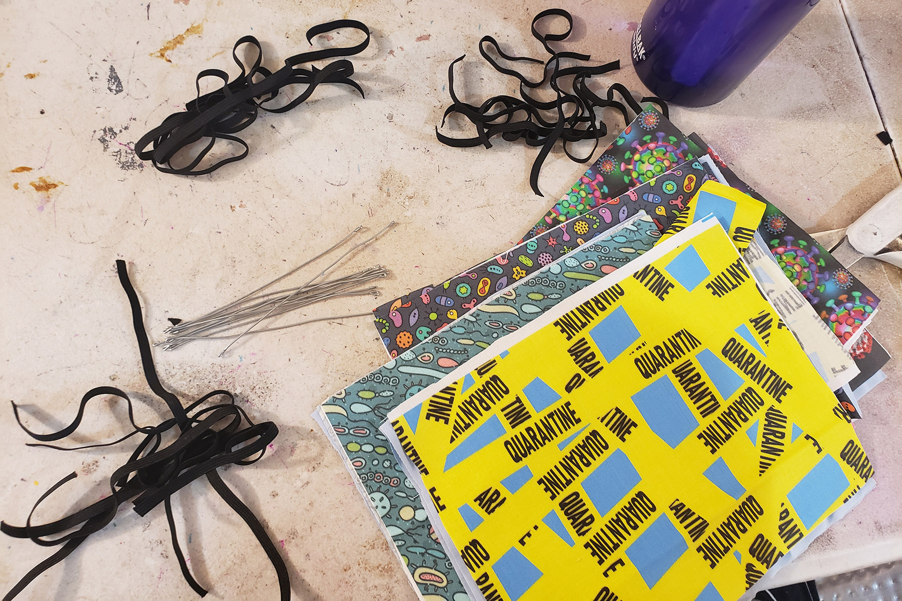Several pieces of brightly coloured fabric, pieces of elastic, and some short lengths of wire.
