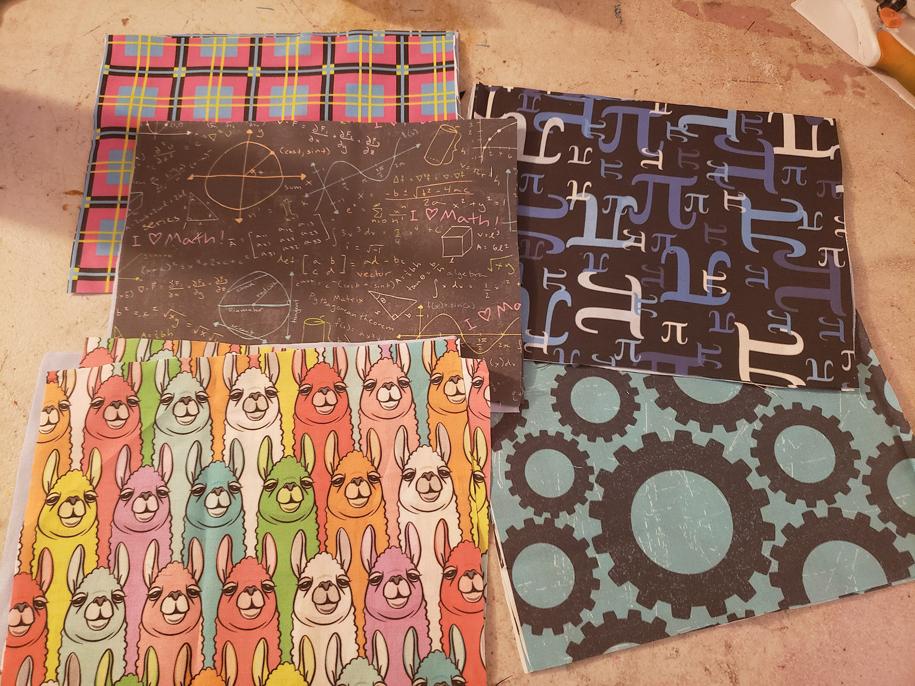 5 rectangles of brightly coloured fabric, spread out on a table.