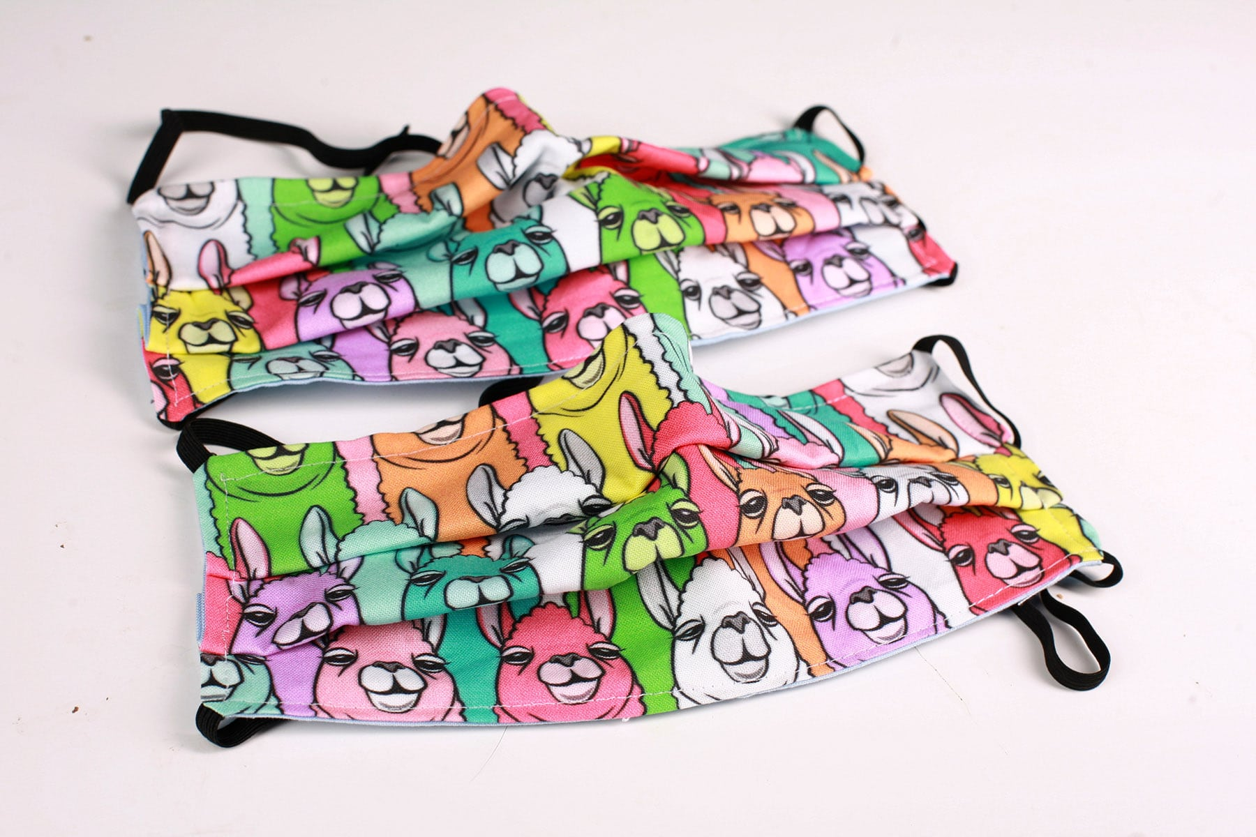 2 brightly coloured fabric face masks with a llamas design on them.