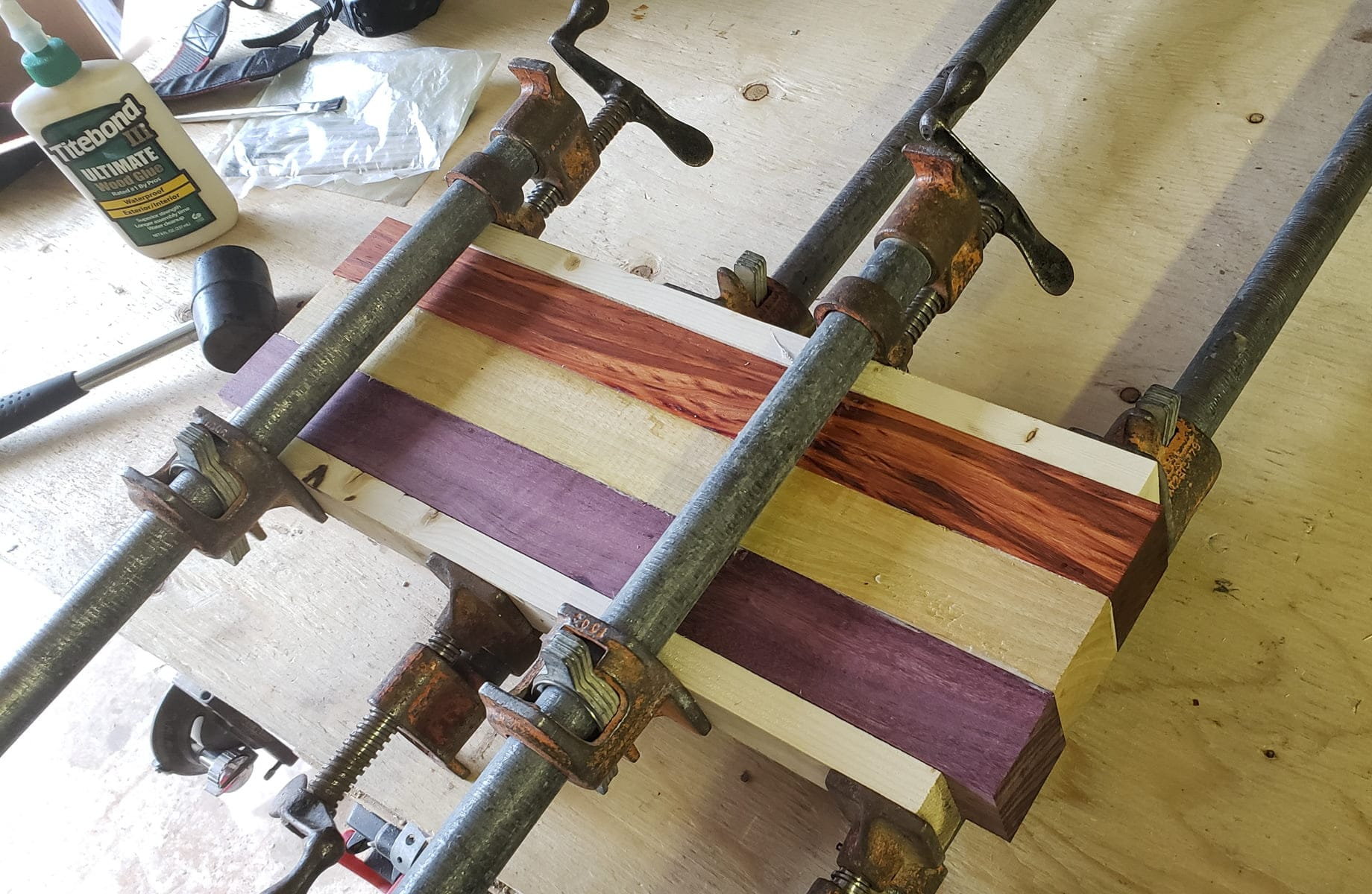 Five boards are clamped together in metal pipe clamps. The outer two boards, which are against the clamps, are cheap pine. The inner three are the high quality boards used in the cutting board.