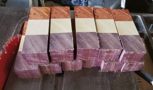 Several strips of wood are seen, each made from three different colors of wood. All of the strips are the same height. The cuts are somewhat rough, from a table saw.