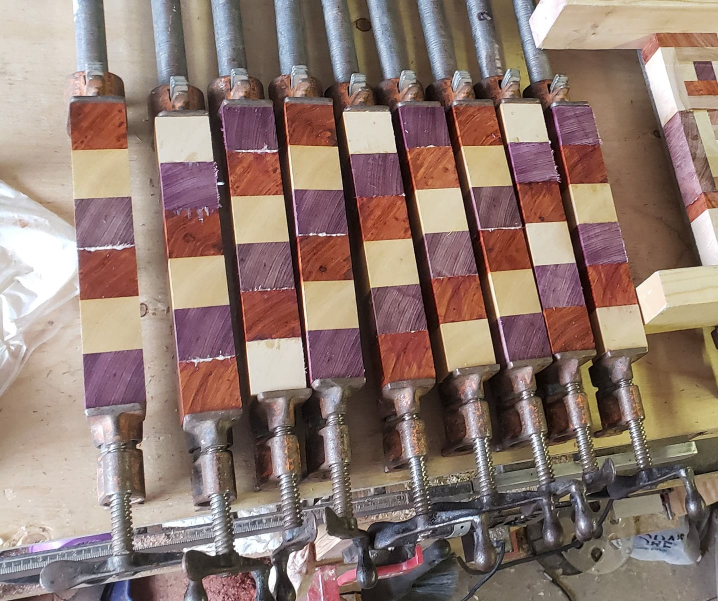 Nine sets of wooden cubes are seen on a table, clamped together in metal pipe clamps. Small amounts of glue are seen at some of the joints.