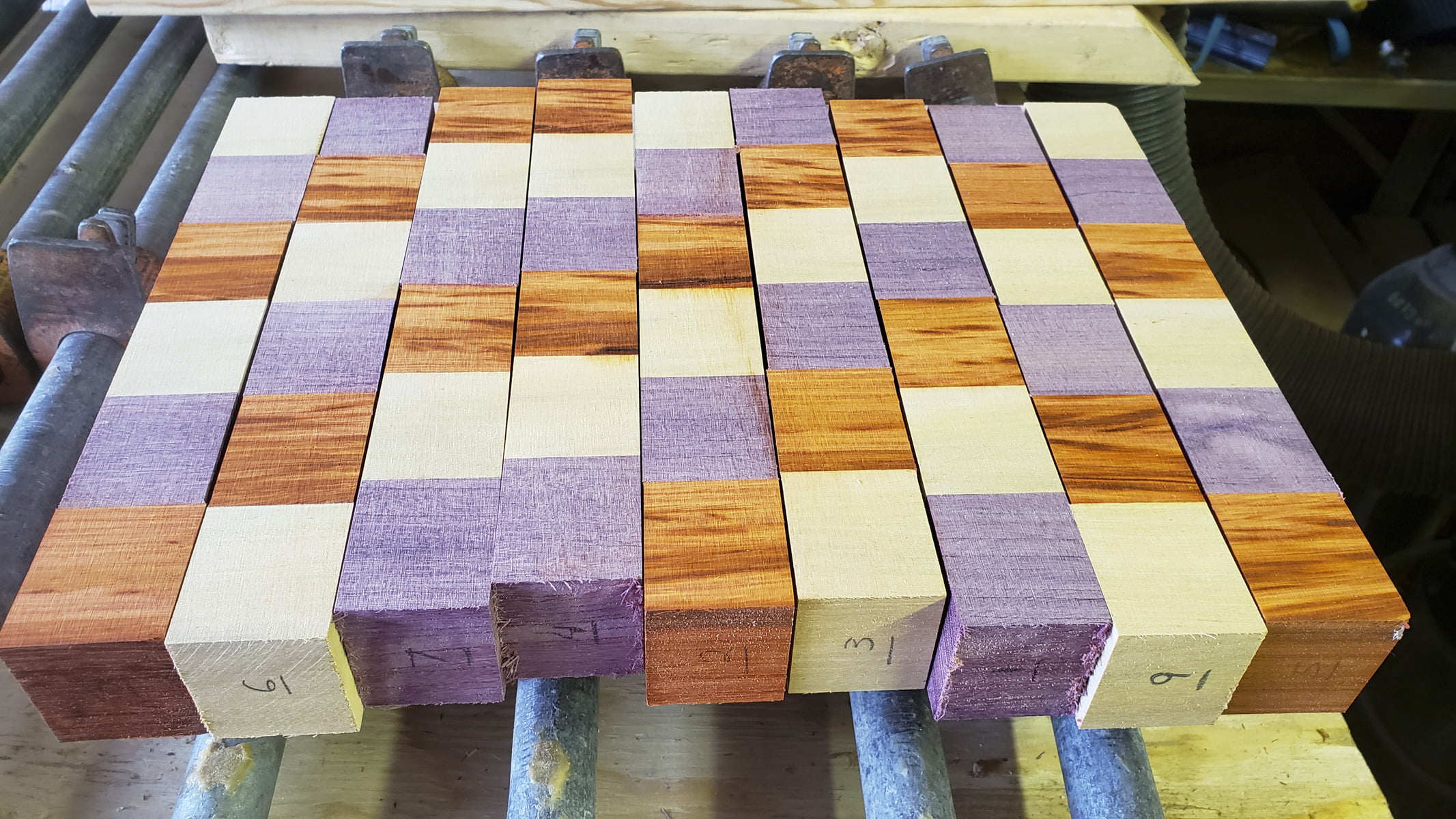 Several strips of wood, comprised of smaller cubes, are seen on a table. Each strip has been sanded to have flat sides.