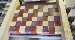 An array of small cubes of wood are clamped together into a large rectangle.