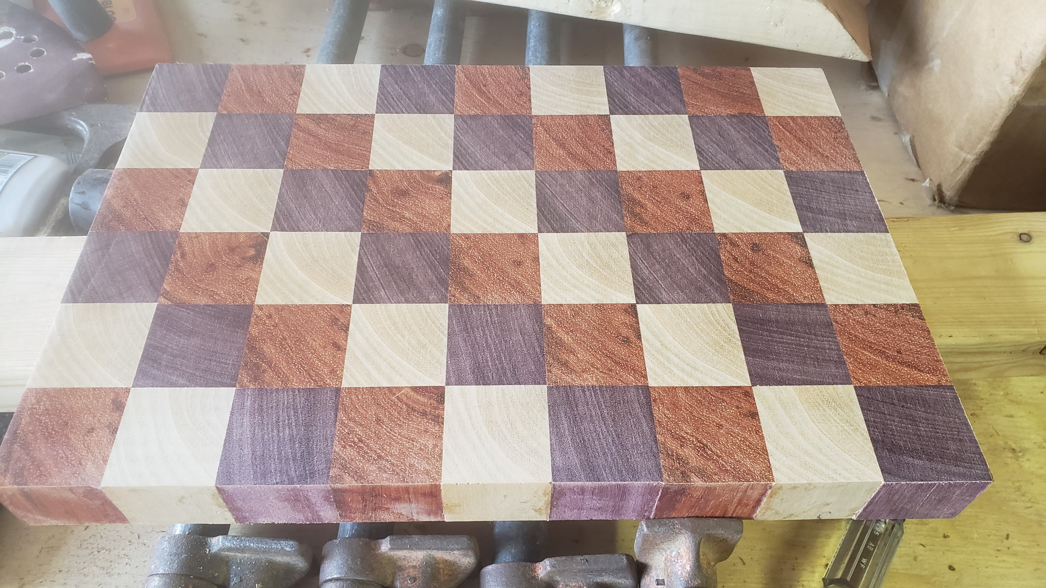 The cutting board, made from an array of small cubes, is seen face up. The surface is smooth but slightly hazy from the rough sanding.
