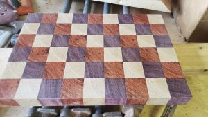The cutting board, made from an array of small cubes, is seen face up. The surface is smooth and slightly shiny from the fine sanding.