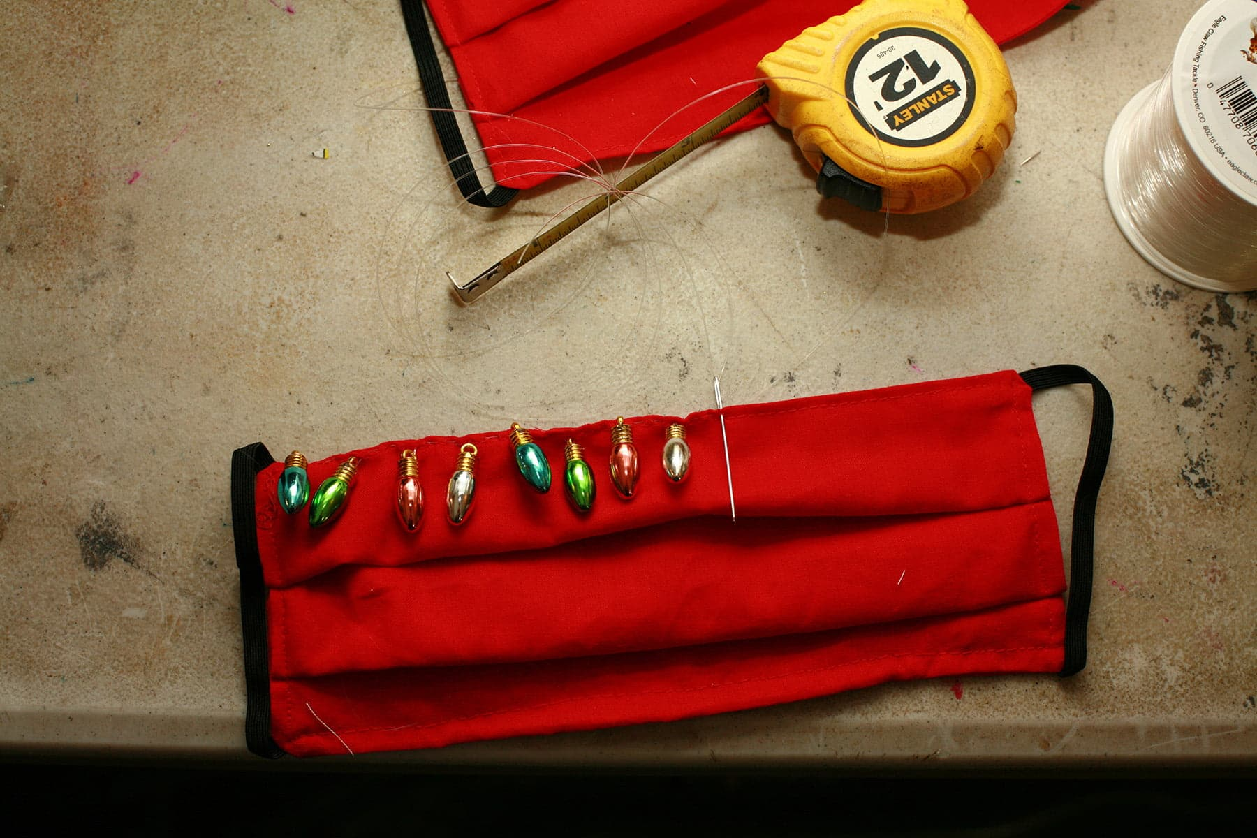 A red mask is laid out on a table, with a line of beading across the top.  There is a needle and fishing line extending off the mask, as the beading is in progress.