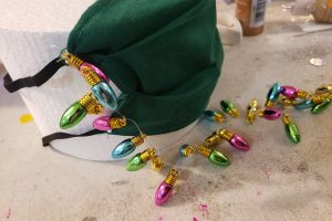 A green mask attached to a round of styrofoam. A string of beads that look like Christmas tree lights is secured to one corner, and laying on the table in front of the mask.