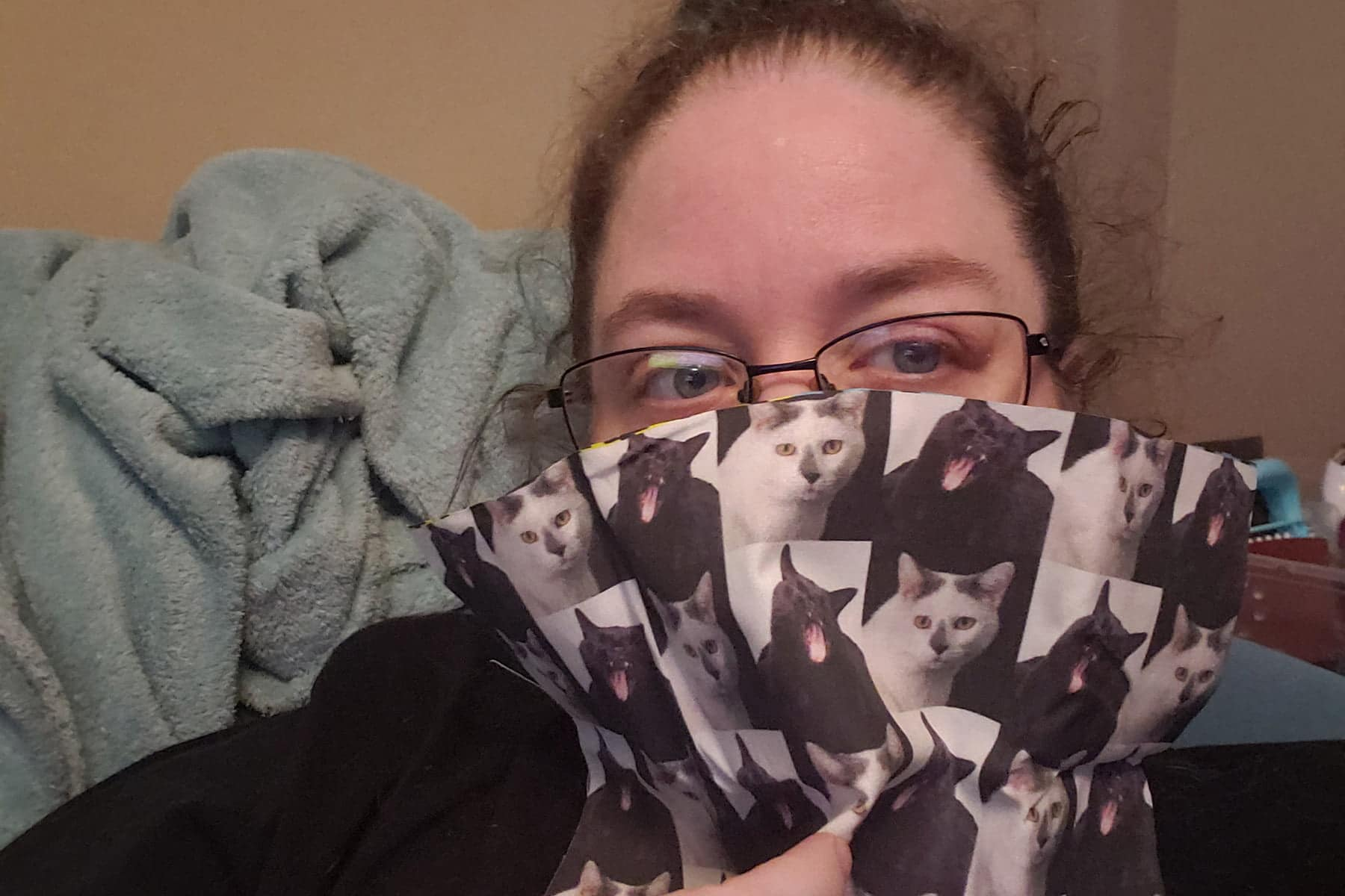 Selfie of a woman holding black and white cat print fabric covering her lower face, as a stand in for a mask.
