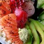 An artfully arranged chirashi bowl - rice with avocados, cucumber, and 3 types of fish slices.