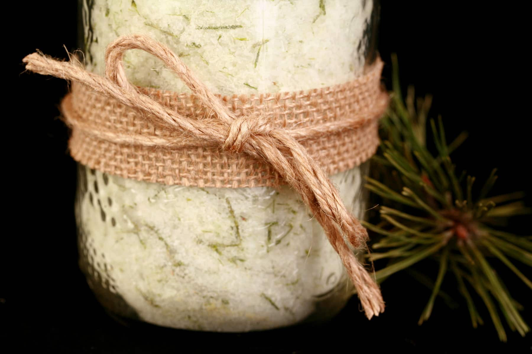 A mason jar filled with a pale green salt that has green flecks of pine needles throughout. It is wrapped with a burlap ribbon and tied with twine.