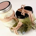 A trio of cedar bath products - a mason jar with bath salts, a smaller jar with green salt scrub, and a green bar of soap. All have flecks of preen pine needles in them. All 3 items are wrapped with burlap ribbon and tied with twine.