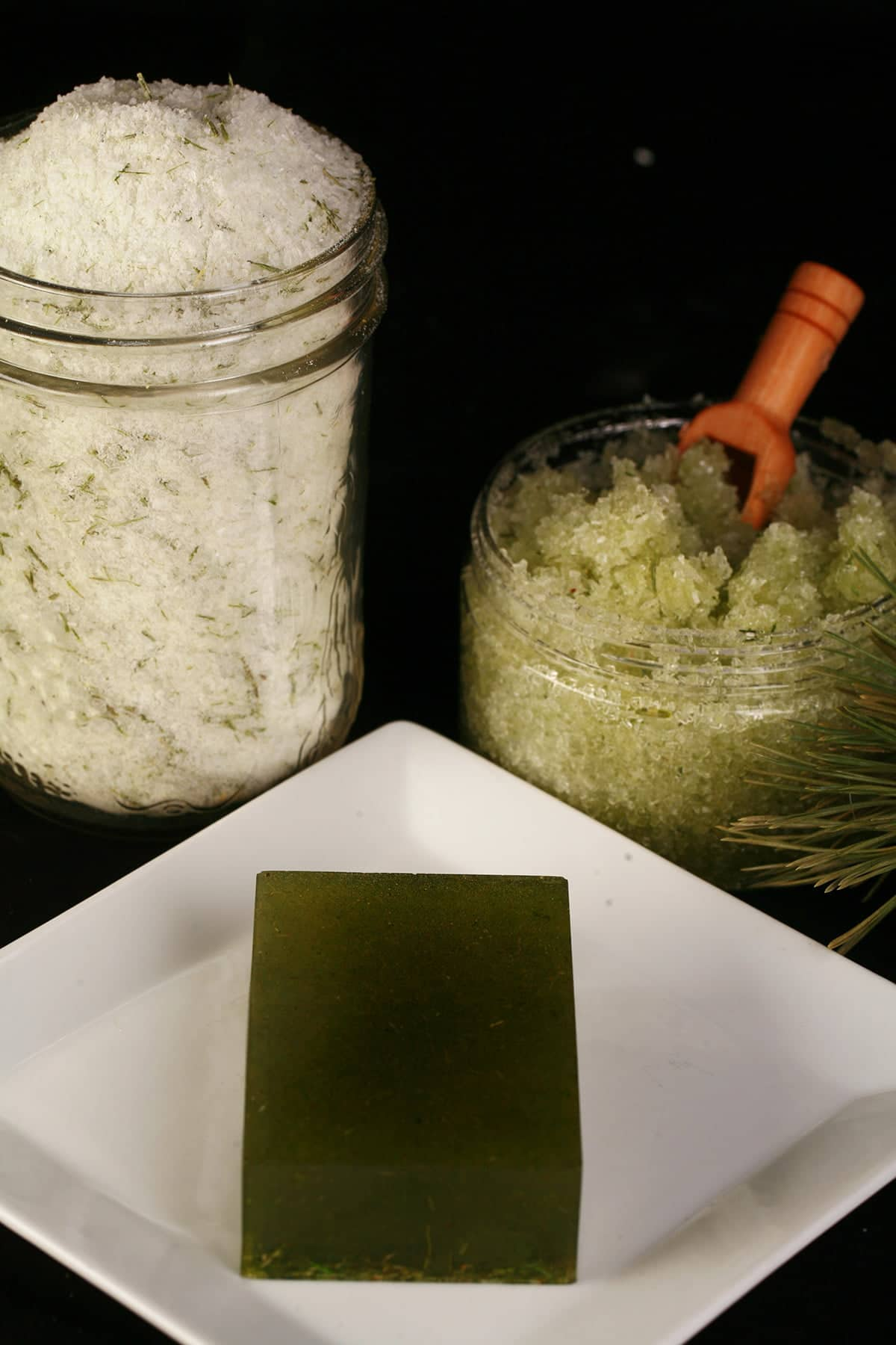 A trio of cedar bath products - a mason jar with bath salts, a smaller jar with green salt scrub, and a green bar of soap. All have flecks of preen pine needles in them.