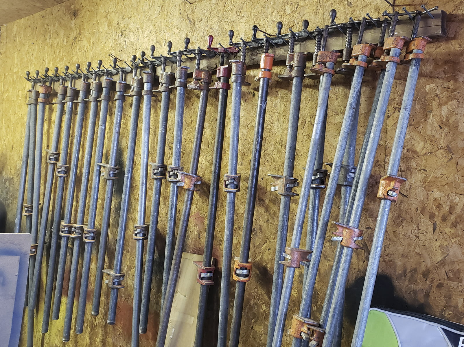 Pipe clamps line the wall of a workshop.