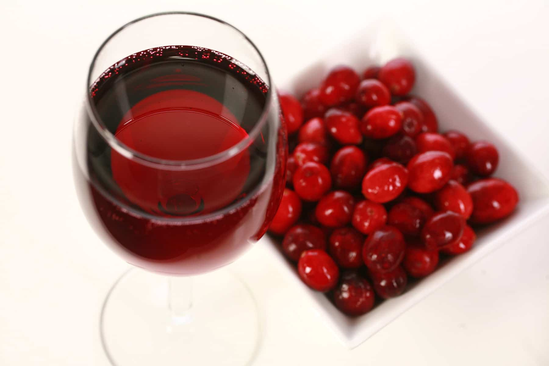 A glass of red wine is pictured next to a small bowl of fresh cranberries, against a white background.