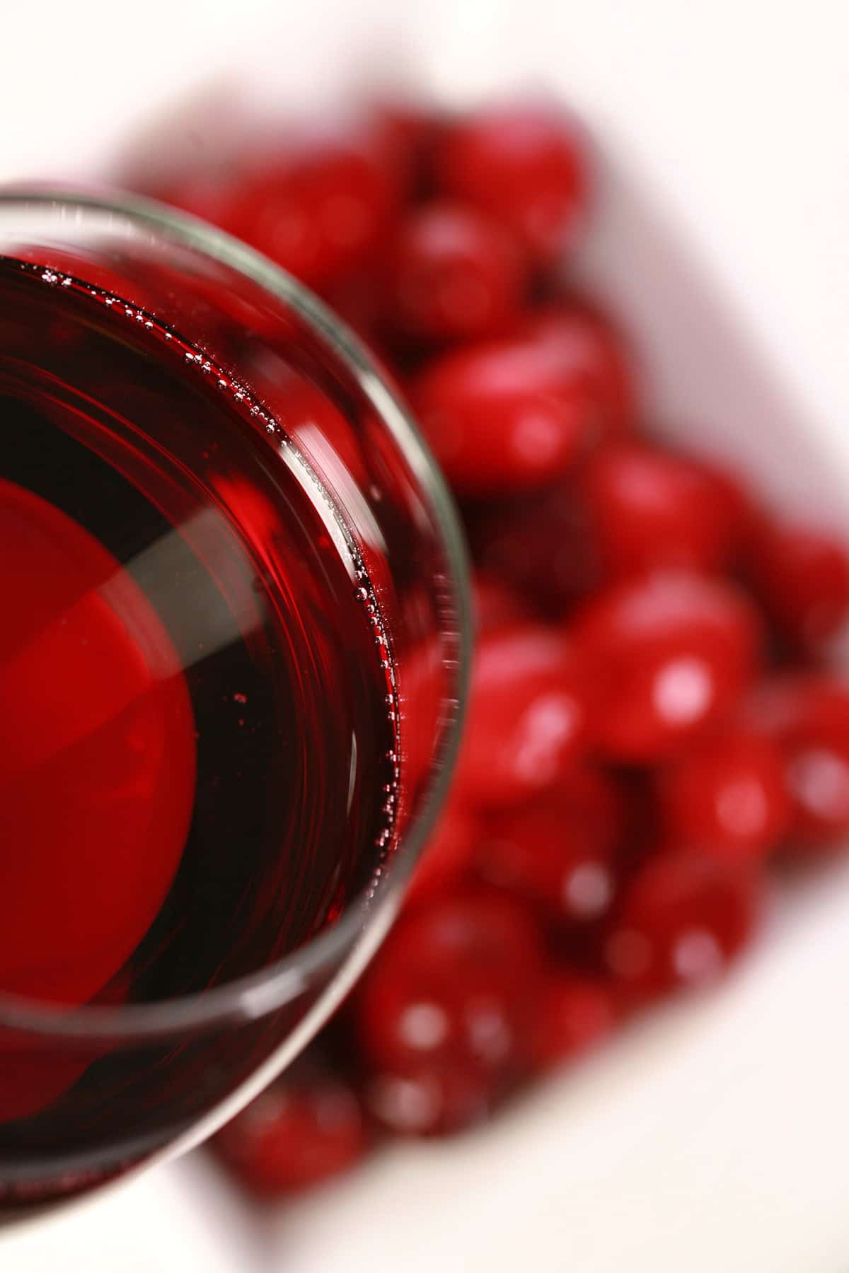 A glass of red wine -made with this cranberry wine recipe - is pictured next to a small bowl of fresh cranberries, against a white background.