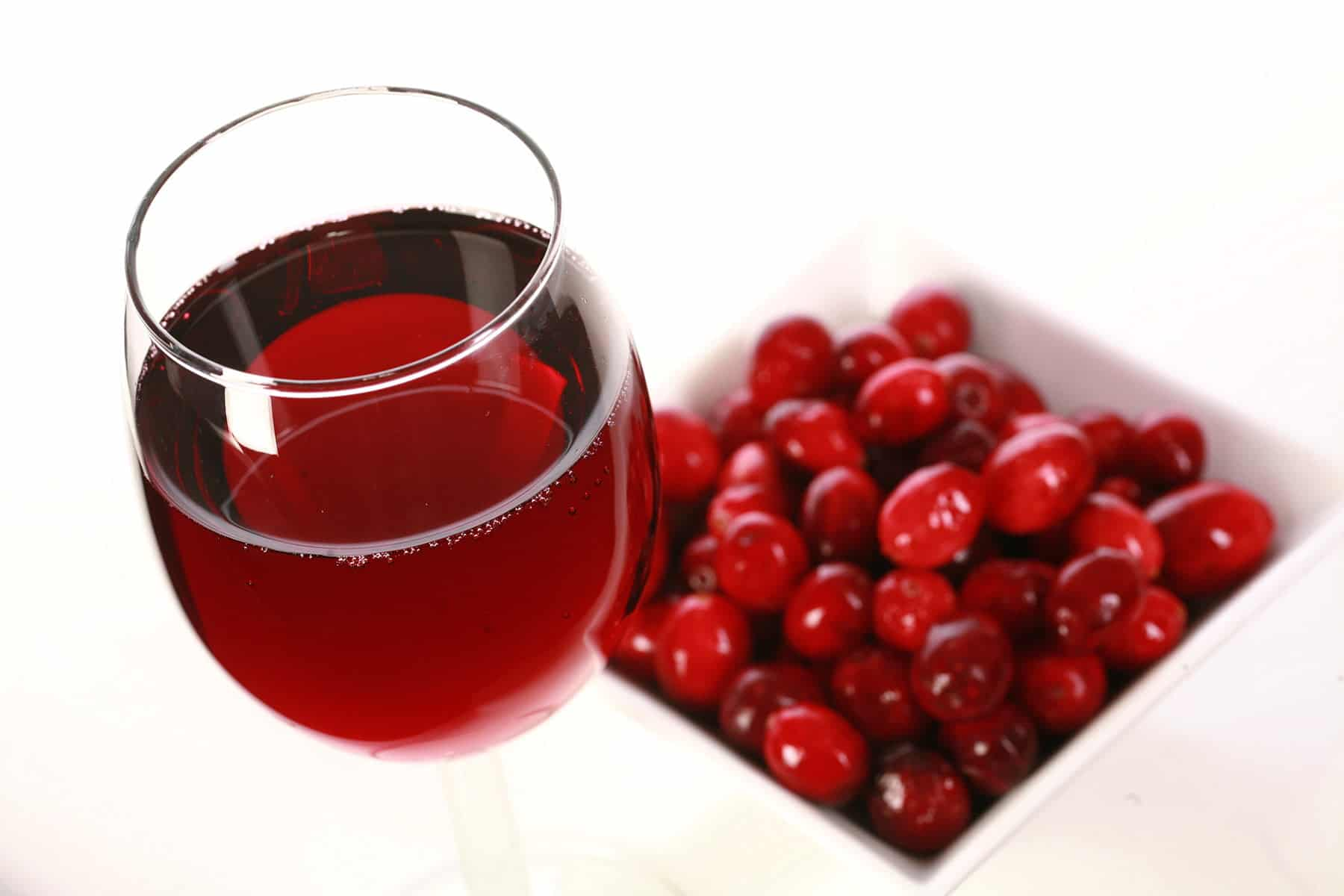 A glass of red wine - made with this cranberry wine recipe - is pictured next to a small bowl of fresh cranberries, against a white background.
