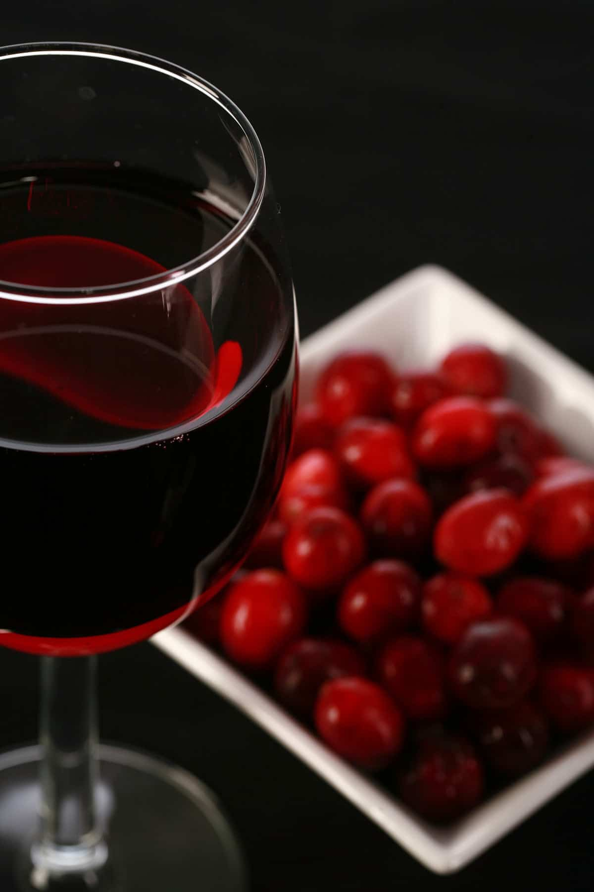 A glass of red wine is pictured next to a small bowl of fresh cranberries, against a black background.