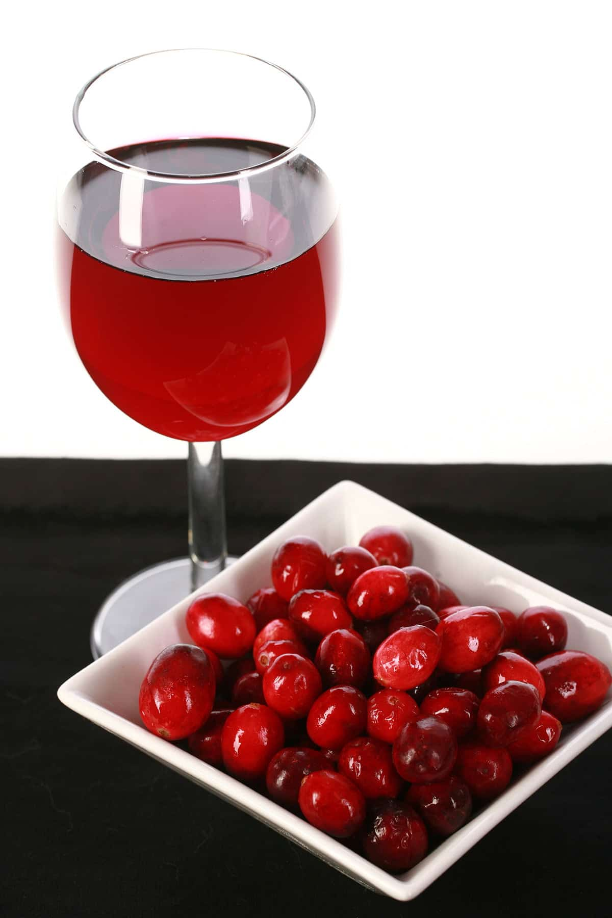 A glass of red wine is pictured next to a small bowl of fresh cranberries, against a white and black background.