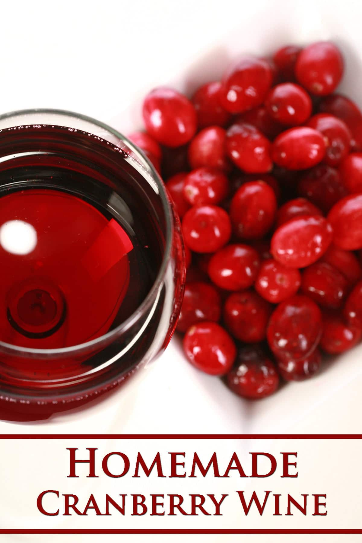 A glass of cranberry wine is pictured next to a small bowl of fresh cranberries, against a white background.