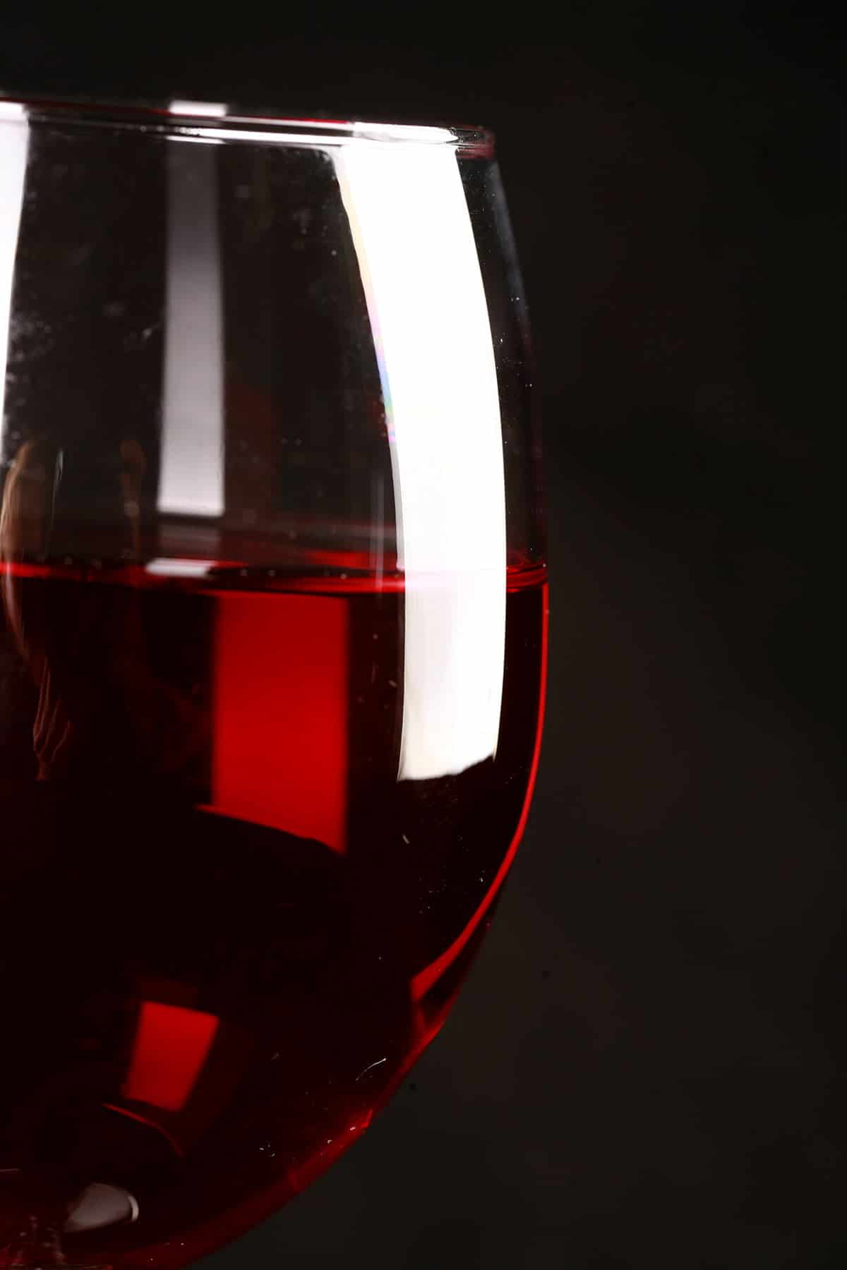 Close up photo of a glass of brilliantly red cranberry wine, in front of a black background.