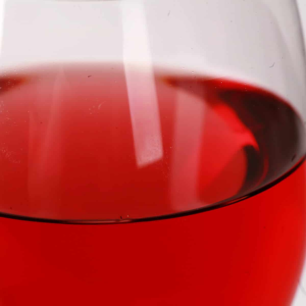Close up photo of a glass of brilliantly red cranberry wine, in front of a white background.