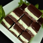 A plate of Creme de Menthe Nanaimo Bars - a 3 layered bar. The top and bottom layers are chocolate, and the middle layer is a green buttercream. They are on a green plate, garnished with a sprig of fresh mint.