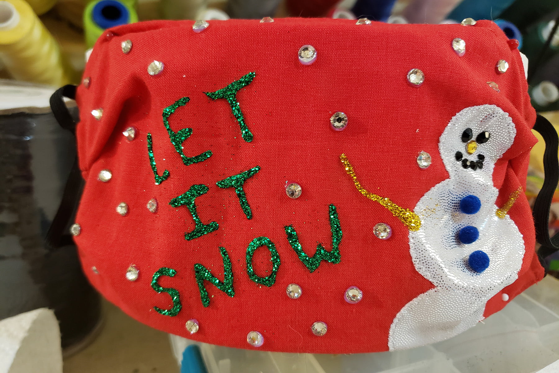"A red mask has a white snowman, and the words ""Let it new"" painted in green glitter.  The whole mask is covered with clear rhinestones."