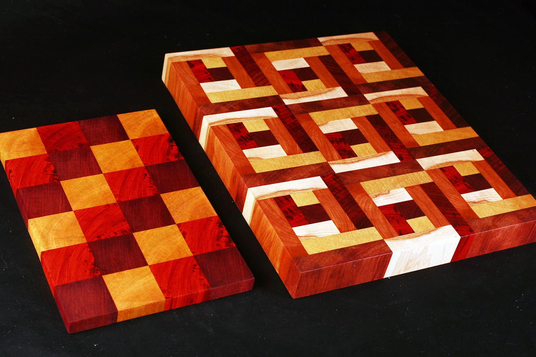 Two fancy cutting boards made of many small pieces of brightly coloured wood.