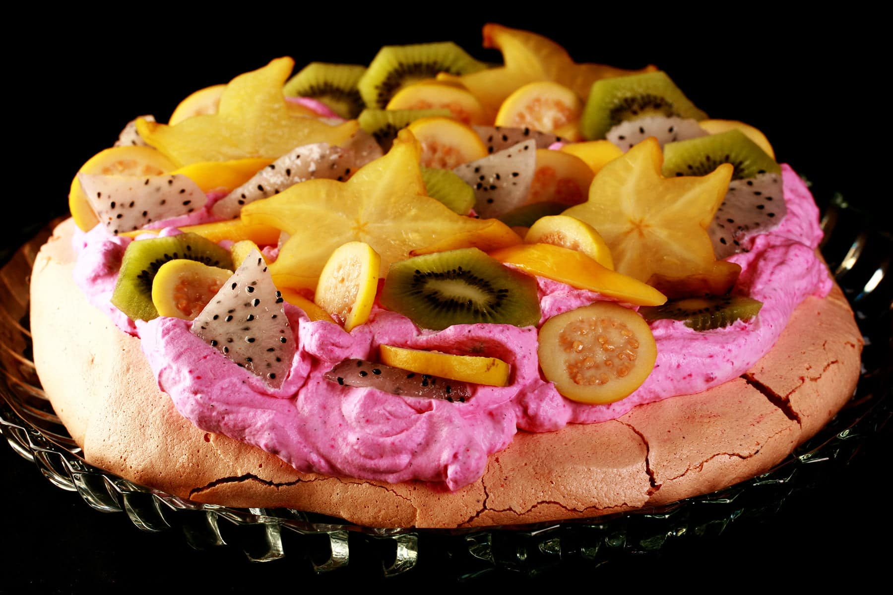 Close up view of a colourful pavlova. It has a light pink meringue base, bright pink whipped cream, and is topped with dragon fruit, star fruit, guava, and mango.