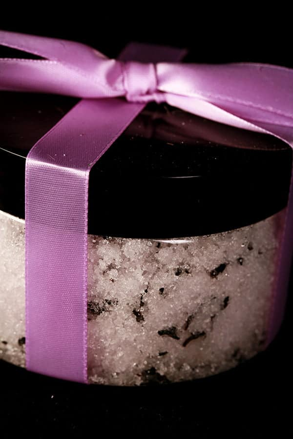 Close up photo of small jar of pale lavender sugar scrub, tied with a lavender satin bow.