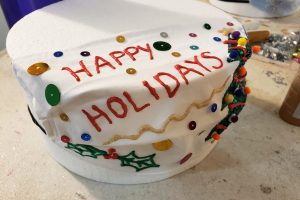"A white mask is stretched over a round of styrofoam. ""Happy Holidays"" is written in red, and the whole mask is covered in gaudy sequins."