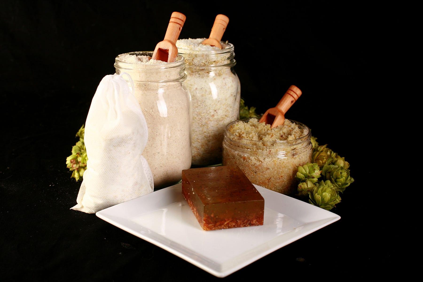 A 4 piece hop spa set, including a bar of hop soap, a canister of hop salt scrub, a jar of hop bath salt, and a jar of hop malted milk bath.