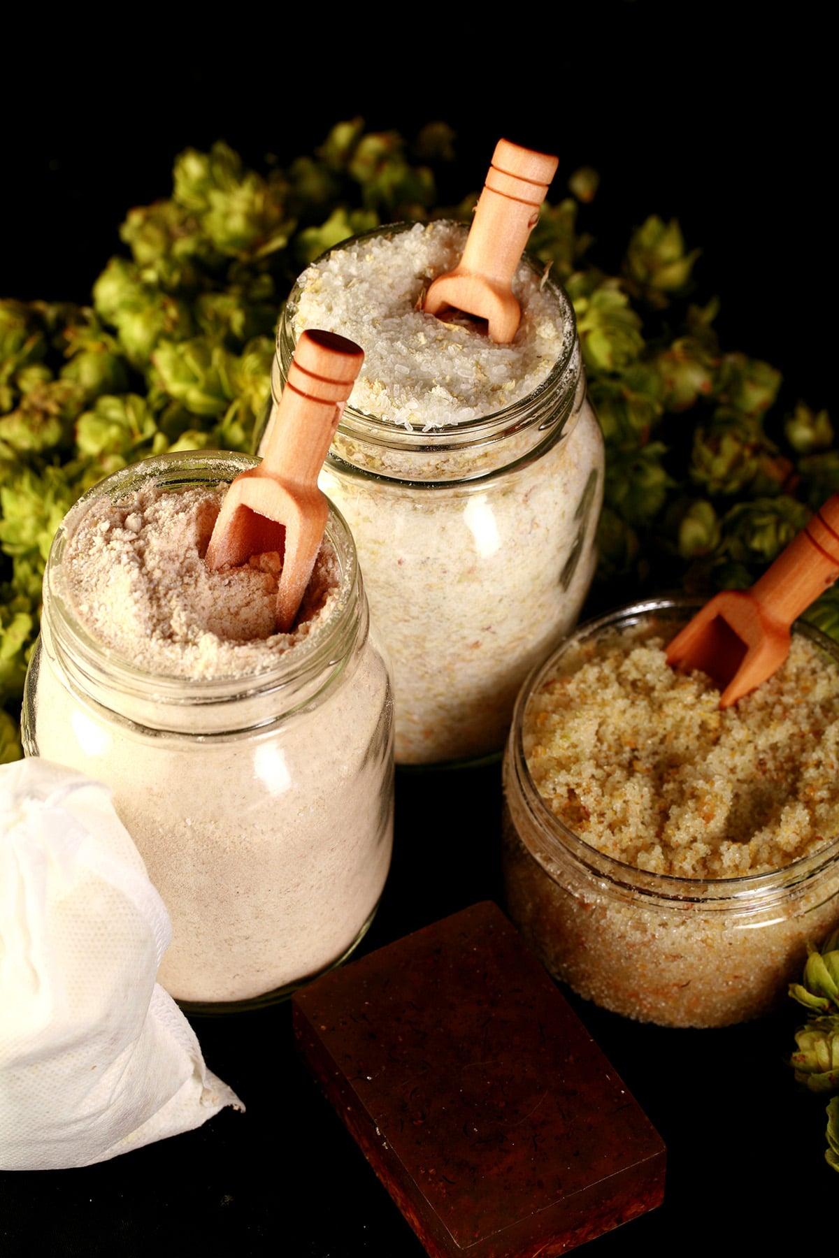 A 4 piece hop spa set, including a bar of hop soap, a canister of hop salt scrub, a jar of hop bath salt, and a jar of hop malted milk bath. A fresh hop bine is in the background.
