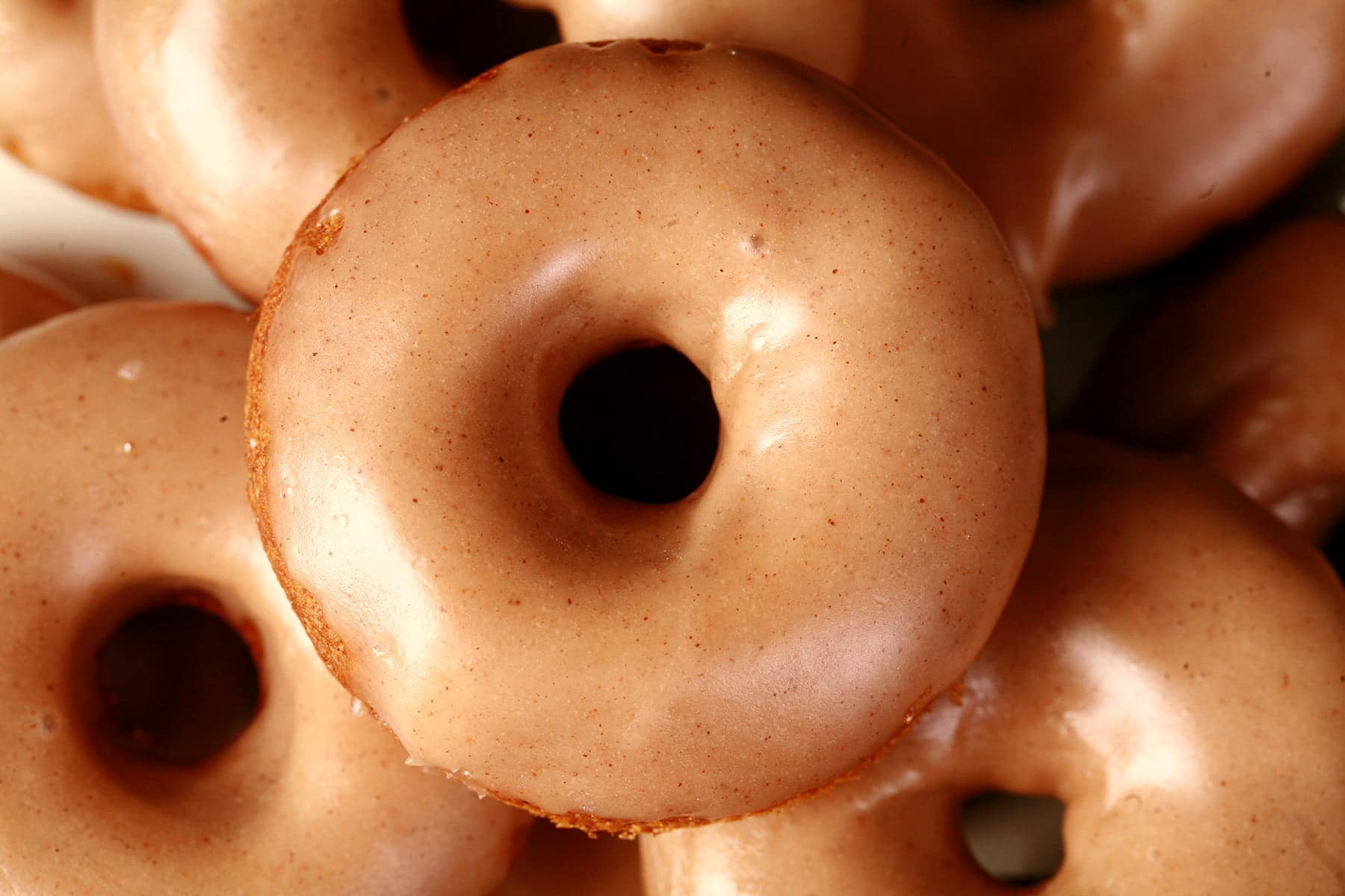 Close up view of gluten-free pumpkin spice mini doughnuts. They are glazed with a tan coloured frosting