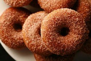 Close up view of gluten-free pumpkin spice mini doughnuts, coated in cinnamon sugar