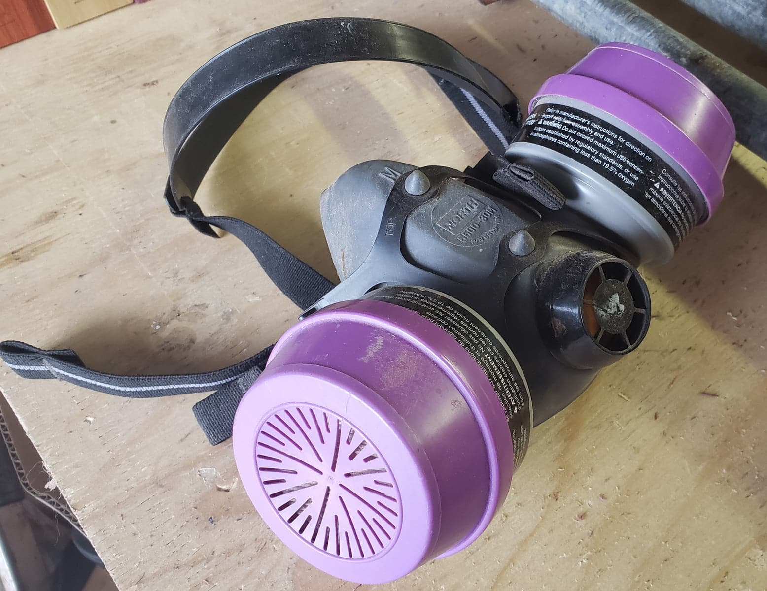 A half mask respirator. The outer cartridges are purple.